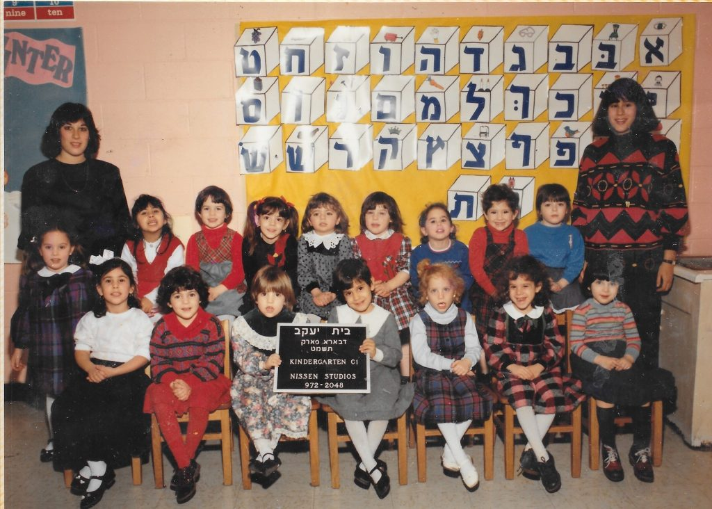 two rows of young girls sitting, flanked by two standing women teachers. Behind them on the wall is the Hebrew alphabet. Two girls in the front row hold a movable-type sign identifying the class.
