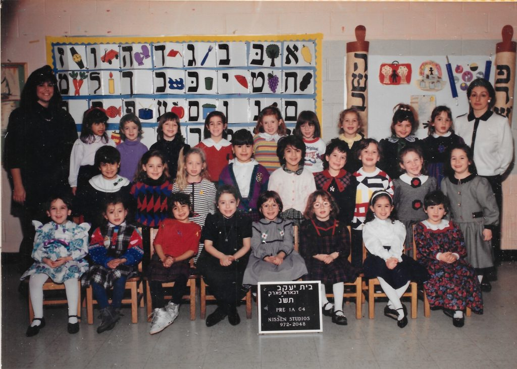 three rows of young girls, one sitting and two standing, flanked by two women teachers. A sign identifying the class is propped up on the floor. Behind them on the wall is the Hebrew alphabet with images next to each letter.