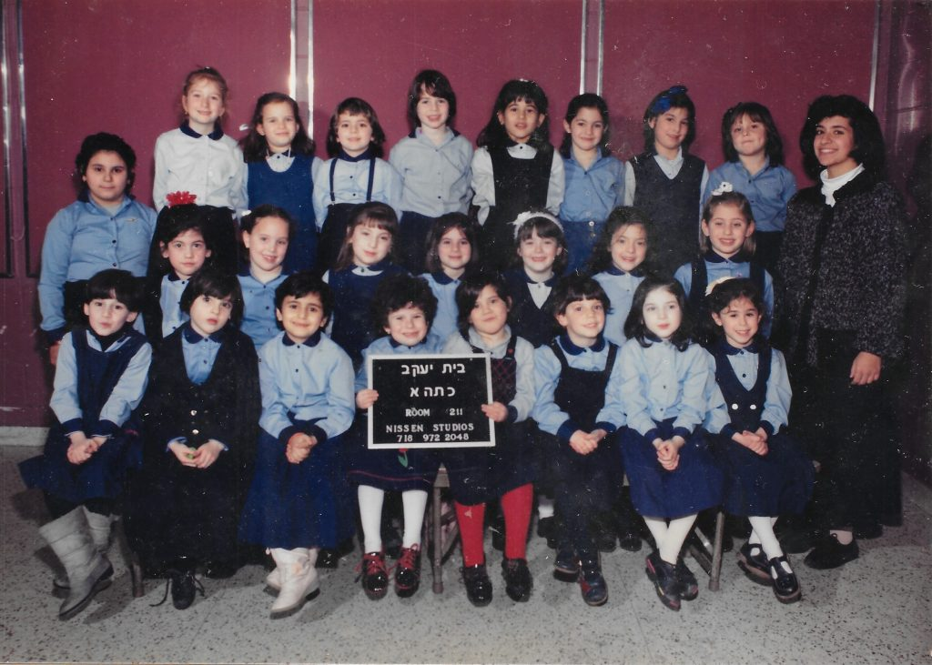 Three rows of girls wearing light blue shirts and dark blue skirts or jumpers. A woman teacher stands to the right. Two girls in the front row hold a sign identifying the class.