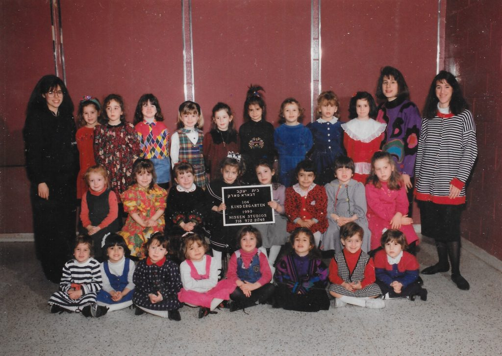 Three rows of girls, one standing on a bench, one sitting on a bench, one sitting on the floor. Two girls in the middle row hold a black-and-white sign identifying the class. Two teachers flank the class on either side.