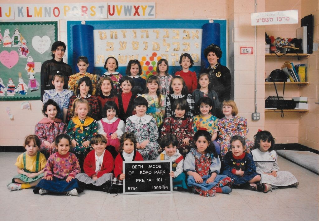 Four rows of girls, one standing on a bench, one standing on the floor, one sitting on a bench, and one sitting on the floor. Two girls in the front row hold a black-and-white sign identifying the class. Two teachers flank the class on either side of the back row.